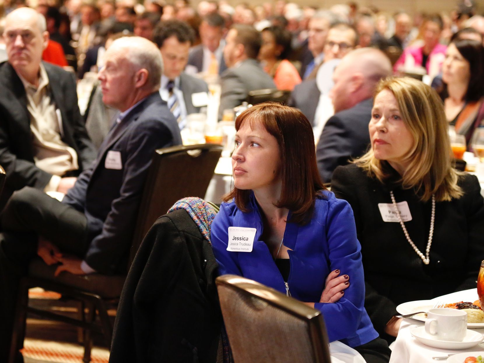Jessica Trudeau, center, and Paige Conley, right, both with the Momentous Institute, listen to  Dallas Mayor Mike Rawlings give his annual State of the City address at a Dallas Regional Chamber luncheon Tuesday, December 5, 2017.