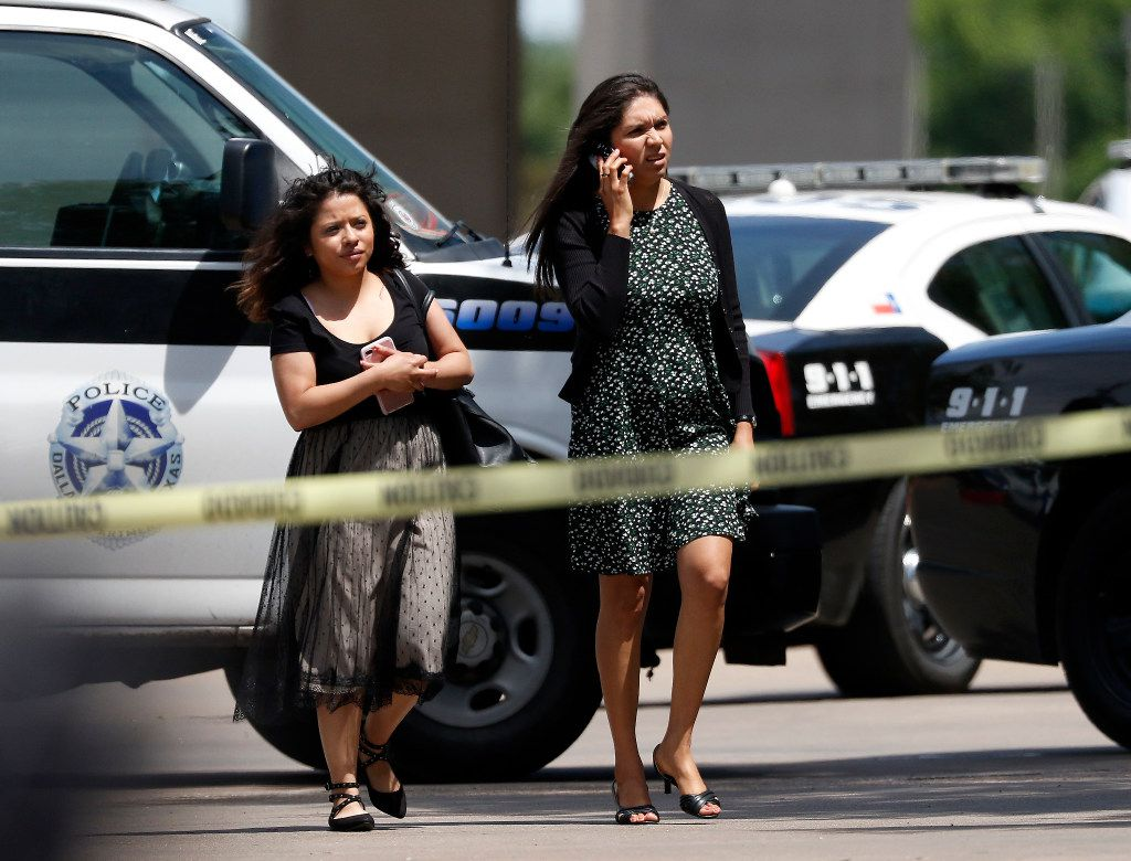 Two people evacuate a shooting scene where police found two people dead at an office building in Lake Highlands near the High Five in Dallas, Monday, April 24, 2017. (Jae S. Lee/The Dallas Morning News)