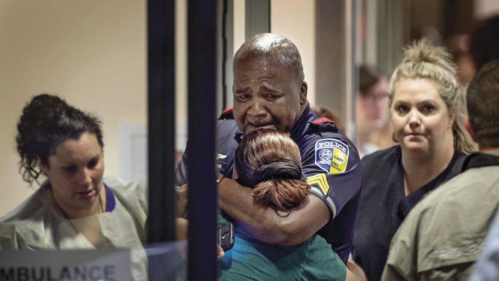 La foto histórica del 7 de julio, el sargento Homer Hutchins abraza a su compañera, la ofiial Shamika Sorrells. A la izq. Juanita Tarango, trabajadora social en Baylor, y Sherry Sutton (der.), jefa de enfermeras en la sala de emergencias.