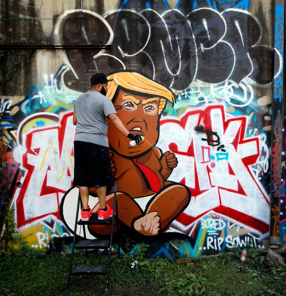 Dallas artist Jeremy Biggers clears his spray can as he paints a caricature of President-elect Donald Trump during GO PAINT DAY at the Fabrication Yard in Dallas, Saturday, November 12, 2016. (Tom Fox/The Dallas Morning News)