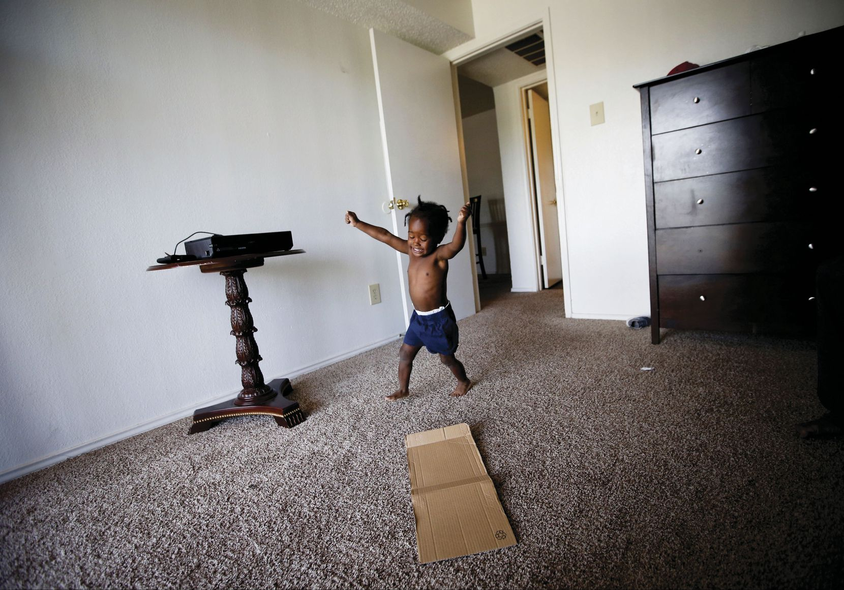 Jordan Miller, 2, runs in circles at his new apartment in Dallas. His father, Joshua Miller, said the new space has his son acting like a 2-year-old again. Before moving into the one-bedroom unit, the Millers lived in a small room at the Family First Men's Shelter.