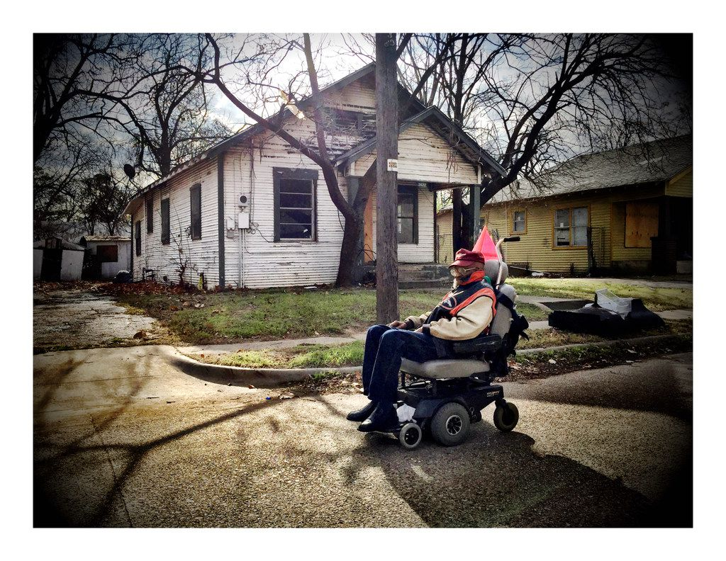 A man on a motorized scooter passes through a South Dallas neighborhood.
