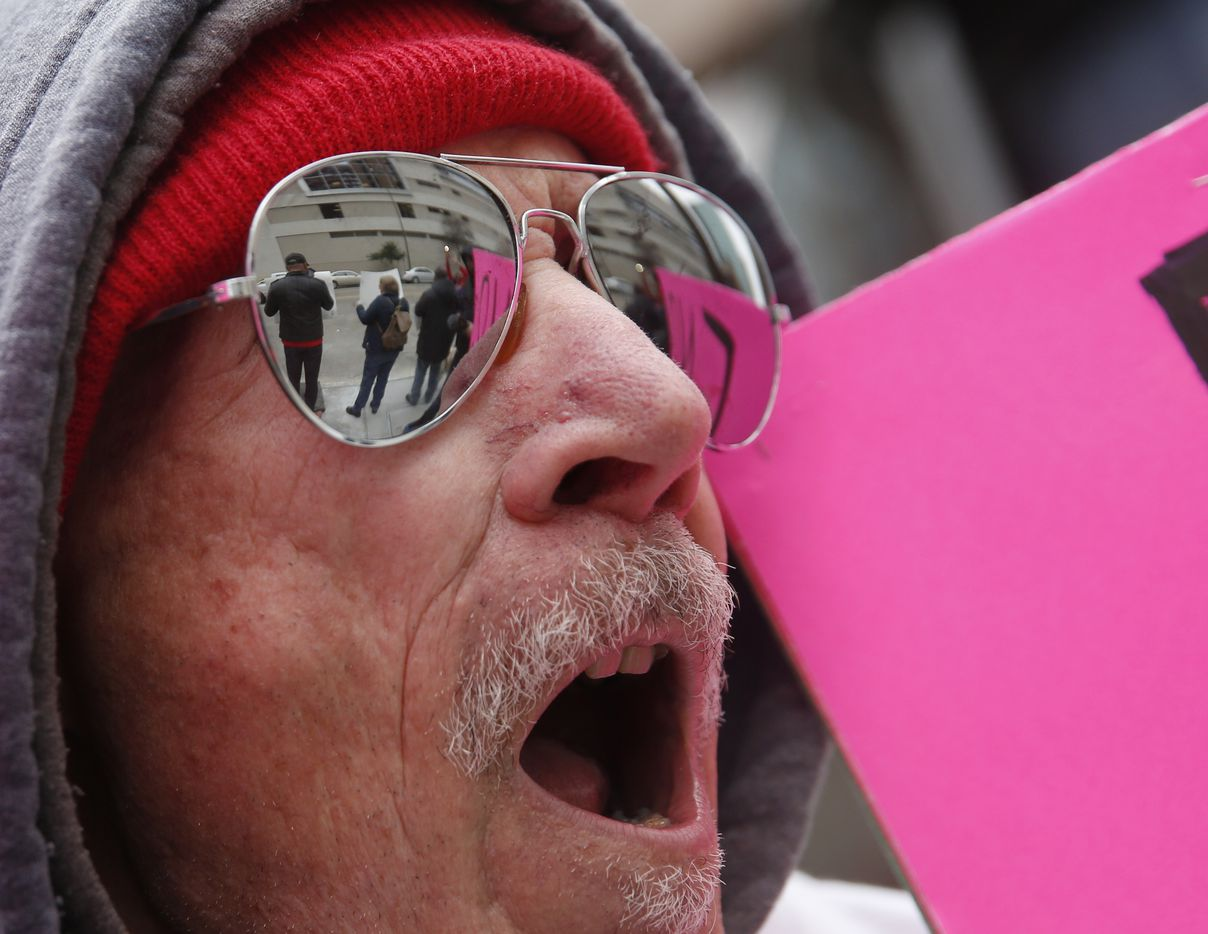 Protestors holding signs are reflected in the glasses of Zen Biasco during a rally in downtown Dallas.