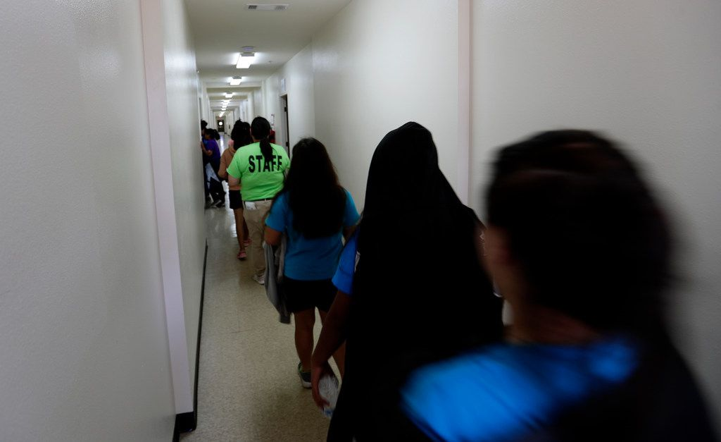 Immigrants walk down the hall of a dormitory at the U.S. government's newest holding center for migrant children in Carrizo Springs, Texas, Tuesday, July 9, 2019.  (AP Photo/Eric Gay)
