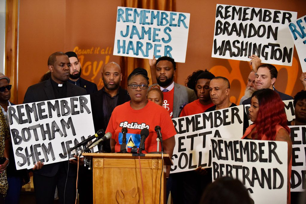 Pastor Michael W. Waters (left) listened as Allison Jean, Botham Jean's mother, called for Dallas police reforms Friday at Joy Tabernacle AME Church. The group, including Bertrum Jean, Botham's father, (right) held signs bearing the names of unarmed people  killed by Dallas police.