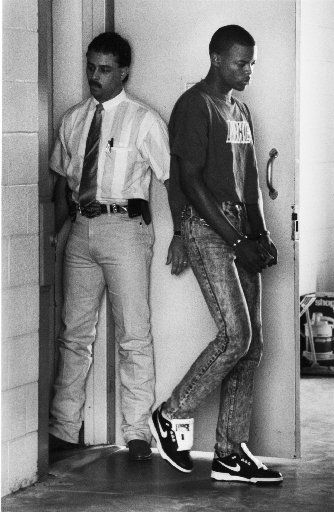 Derric Evans , the former Carter HS football player, is transfered from the Duncanville police station to Lew Sterret after turning himself in on June 23, 1989, after being charged with an armed robbery in Duncanville. Left is investigator Alvin Sims of Duncanville PD.