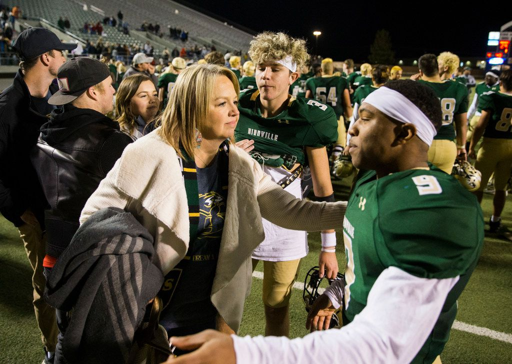 Birdville running back Laderrious Mixon (9) gets a hug from Josie Earle after a 29-27 win over Fort Worth Boswell on Thursday, November 15, 2018 at the Birdville Fine Arts Center in North Richland Hills, Texas. The Earle family, including quarterback Stone Earle (3), adopted Mixon. (Ashley Landis/The Dallas Morning News)