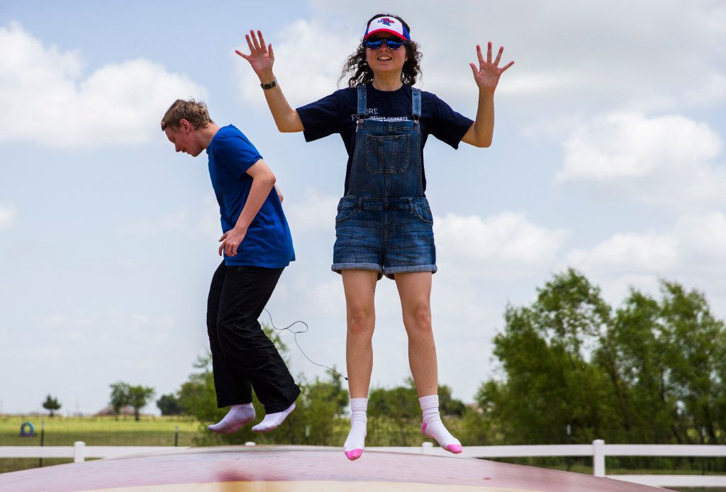 Maddie Blanton, 22, right, and Tobias Gaston, 16, who are both autistic, jump on a giant jumping pillow during a trip to the Gentle Zoo.