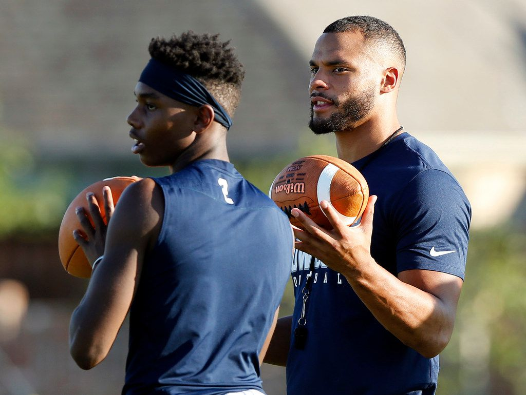 Dallas Cowboys quarterback Dak Prescott watches as Malik Bailey (2) throws a pass as he filmed a Chunky Soup commercial at the schools practice field, Monday, September 17, 2018. (Tom Fox/The Dallas Morning News)