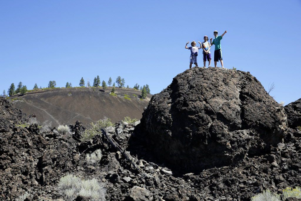 Visitors climb the natural formations at the Newberry National Volcanic Monument in Deschutes National Forest near Sunriver, Ore.