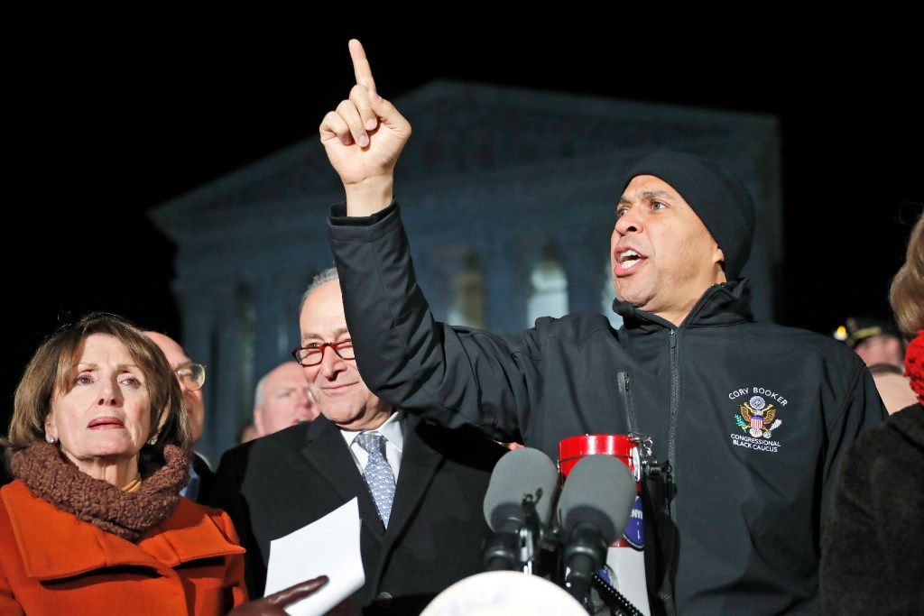 Sen. Cory Booker, D-N.J., (right), House Minority Leader Nancy Pelosi, Senate Minority Leader Chuck Schumer were among those who pledged to fight the president's executive order. (Alex Brandon/The Associated Press)