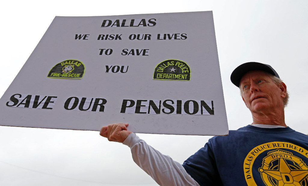 Andy Paris, who retired after serving 33 years as a Dallas Police officer, holds a sign during a rally against Mayor Mike Rawlings' letter, which asked taxpayers to support in making changes to a proposed Dallas Police and Fire pension bailout, at the City Hall in Dallas, Wednesday, April 26, 2017. (Jae S. Lee/The Dallas Morning News)