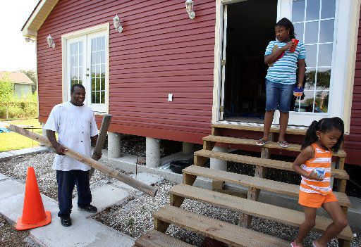 In August 2008, James Ackerson prepared to board up his newly rebuilt home in the 9th Ward in New Orleans as his daughters, Jardyn and Jaetlya, carried last-minute food supplies to the family car.