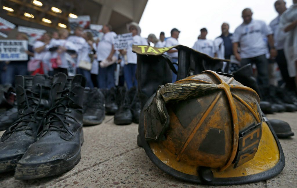 A helmet and boots of Dallas police and fire retirees lay on the ground at a rally at City Hall earlier this year.
