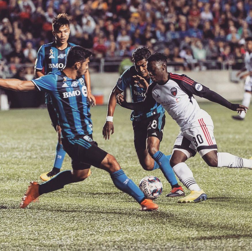 Adonijah Reid (in white) takes on three Montreal Impact defenders in the 2018 CapCity Cup.