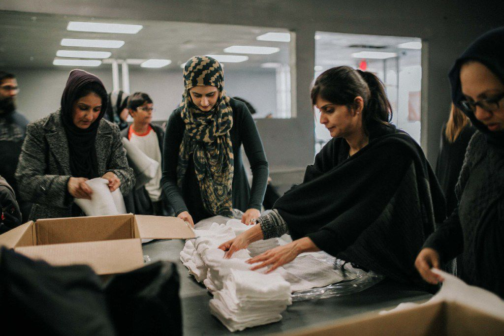Muslim volunteers in Allen pack survival kits for the homeless in Dallas on an overcast Saturday. The packets include bottled water, socks, deodorant, toothpaste, a toothbrush, a washcloth and a blanket.