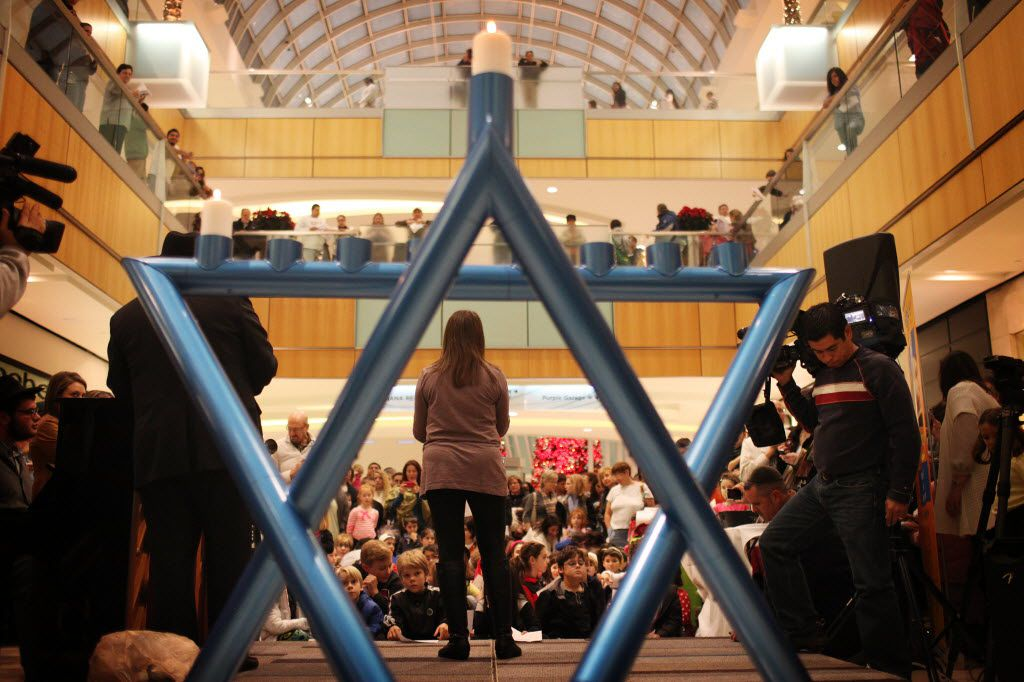 Families gathered to watch the ceremonial lighting of the community menorah at the Galleria.