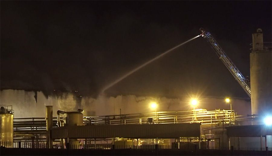 A Mesquite firefighter high atop a ladder pours water onto a fire early Monday at the Fritz Industries chemical warehouse early Monday.