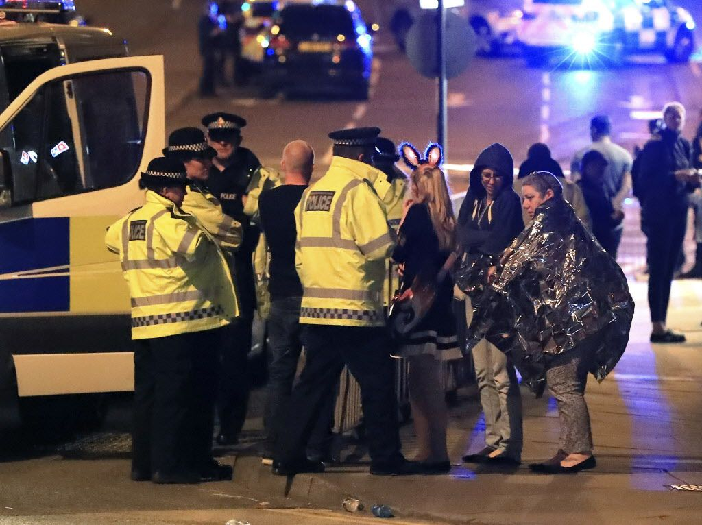 Emergency services personnel speak to people outside Manchester Arena after reports of an explosion at the venue during an Ariana Grande concert in Manchester, England, Monday, May 22, 2017. Several people have died following an explosion Monday night at an Ariana Grande concert in northern England, police and witnesses said. The singer was not injured, according to a representative. (Peter Byrne/PA via AP)