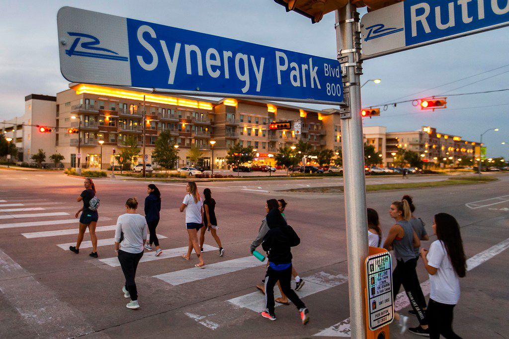 """Pedestrians cross Synergy Park Blvd. toward the Northside mixed use development on Tuesday, July 10, 2018, in Richardson, Texas. DART has often referred to mixed-use developments like Northside as """"transit-oriented"""", but The Cotton Belt line which will be just to the north of these new buildings won't supply trains until 2022. UTD student  resident growth is driving the development, which is currently served by a DART bus line on Synergy Park Blvd. (Smiley N. Pool/The Dallas Morning News)"""