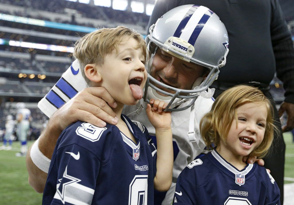 Hawkins Romo makes a face as he takes a photo with Dallas Cowboys quarterback Tony Romo as Rivers Romo looks on before a game between the Dallas Cowboys and Baltimore Ravens at AT&T Stadium in Arlington on Sunday, November 20, 2016. (Vernon Bryant/The Dallas Morning News)