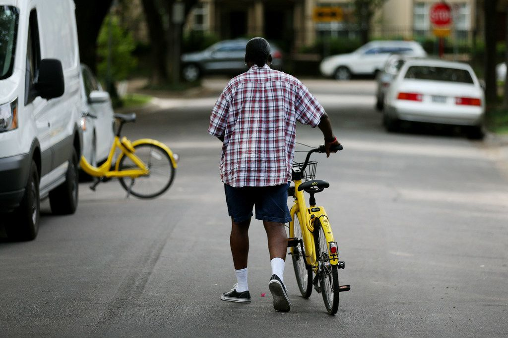 """Maurice Clark, a """"rebalance technician"""" with bike-share company Ofo, rebalances bikes along Buena Vista Street in Uptown. Ofo, a Beijing-based bike-share company, started in 2014 and launched in Dallas in October 2017. The company said it has about 5,000 bikes in Dallas. (Andy Jacobsohn/The Dallas Morning News)"""