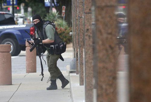 El pistolero, enmascarado y con equipo militar, camina hacia la corte federal Earle Cabell, antes de la balacera. TOM FOX/DMN