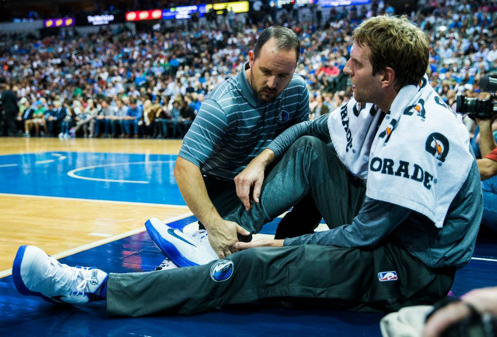 Dallas Mavericks forward Dirk Nowitzki (41) has his right achilles tendon looked at by a trainer on the sideline during the second quarter of their game against the Portland Trail Blazers on Friday, November 4, 2016 at the American Airlines Center in Dallas.  (Ashley Landis/The Dallas Morning News)