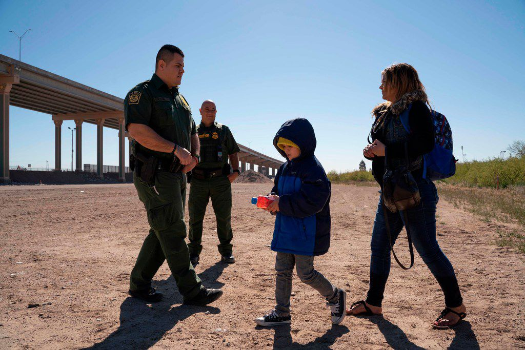 A mother and her son turn themselves in to US Border Patrol agents to claim asylum after crossing the Rio Grande in El Paso, Texas on March 19, 2019.