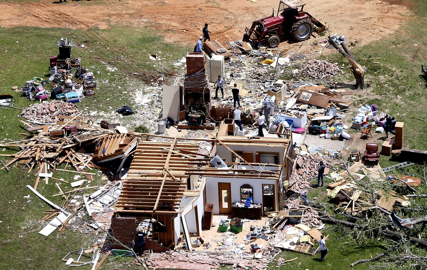 People clean up the debris inside homes destroyed by yesterday's tornado in Emory, Texas, Sunday, April 30, 2017.