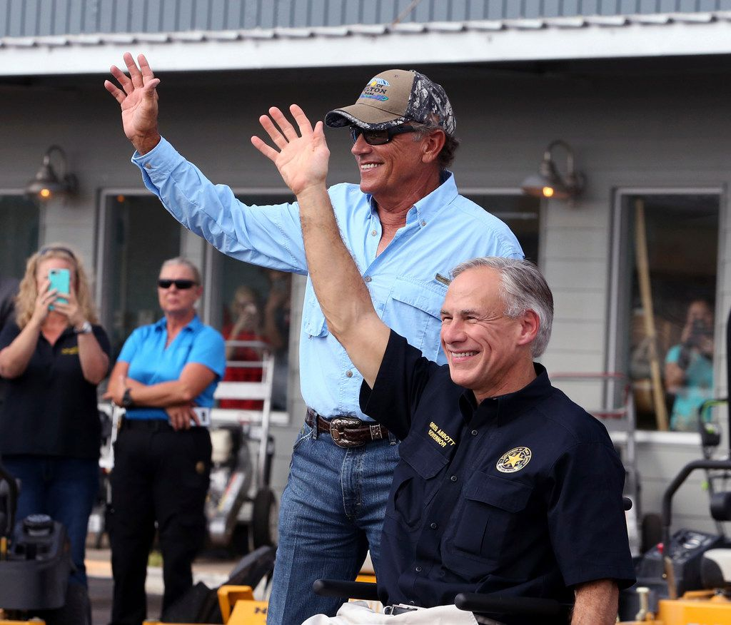 George Strait (left) and Texas Gov. Greg Abbott wave to the crowd in Rockport during a visit with residents affected by Hurricane Harvey last year. Texas coastal towns where Harvey made landfall are working to restore tourism and other economic attractions nearly five months after the storm.
