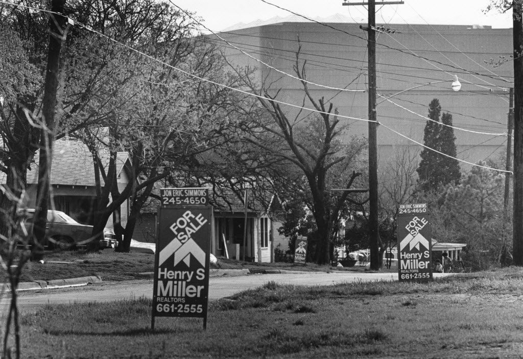 "Real estate ""for-sale"" signs are shown in the Little Mexico neighborhood of Dallas in 1981.  The World Trade Center can be seen in the background."