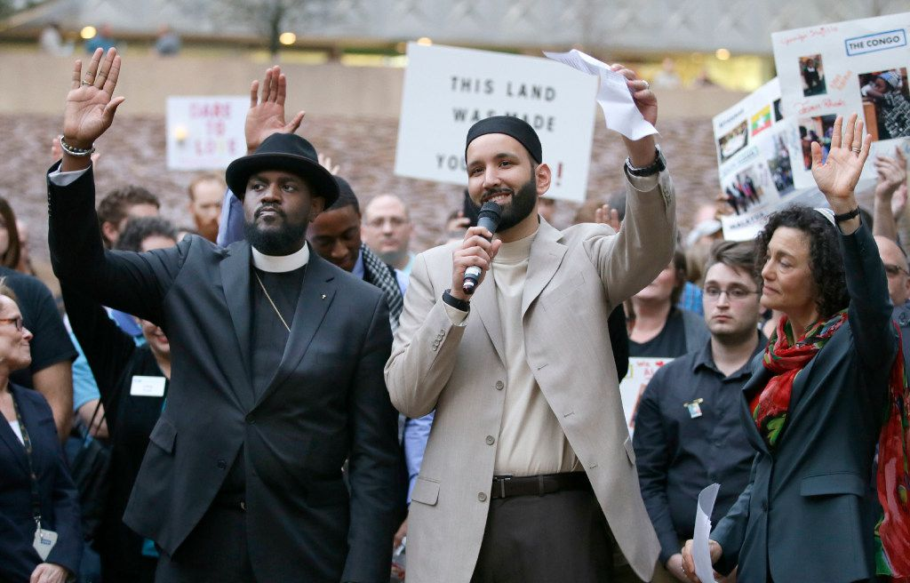Iman Omar Suleiman, center, raises his hand with Rabbi Nancy Kasten, right, and the Rev. Michael W. Waters while speaking before a candlelight vigil at Thanksgiving Square in downtown Dallas, Monday, Jan. 30, 2017.  (AP Photo/LM Otero)