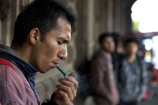 Un activista por la legalización de la marihuana fuma en el pórtico de un edificio gubernamental en frente de la Suprema Corte de México. (AP/REBECCA BLACKWELL)