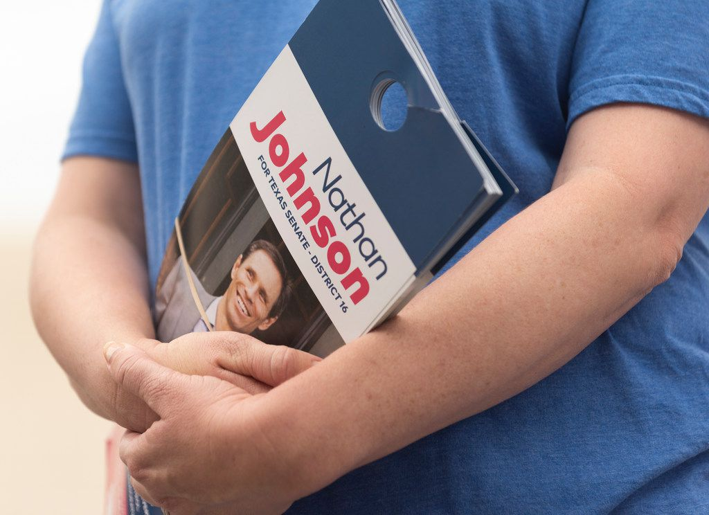 A Nathan Johnson volunteer holds door hangers as she and others prepare to canvass a neighborhood on Monday, Sept. 3, 2018.  Johnson is running against Don Huffines for the Texas Senate in district 16. (Rex C Curry/Special Contributor)