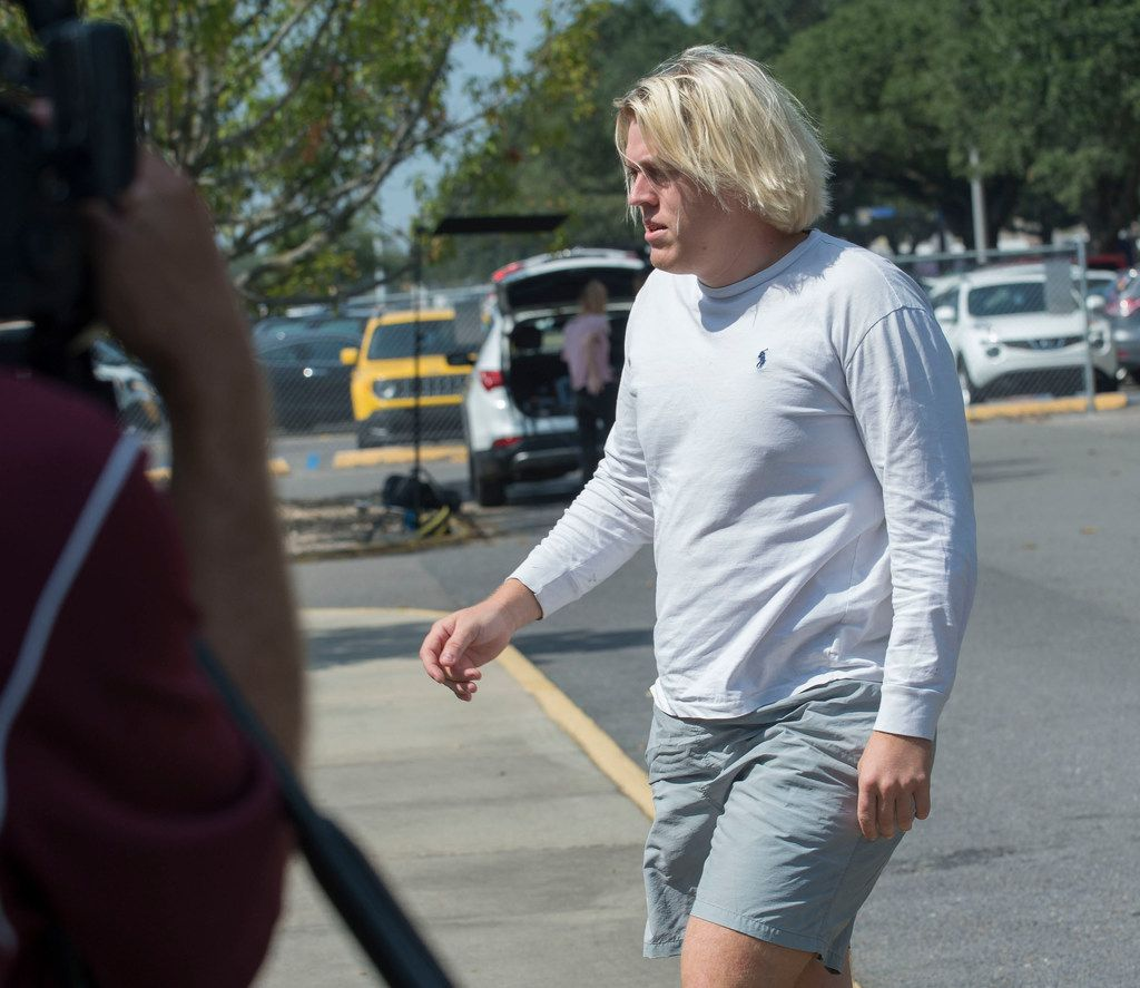 Sean Paul Gott walks toward the entrance to the LSU Police Dept., before being booked on a hazing charge on Wednesday, Oct. 11, 2017 in Baton Rouge, La.  Ten members of the Phi Delta Theta fraternity were arrested Wednesday on hazing charges in the death of Maxwell Gruver, a Louisiana State University fraternity pledge whose blood-alcohol content level was more than six times the legal limit for driving, officials said.  Matthew Alexander Naquin also faces a negligent homicide charge.   (Travis Spradling/The Advocate via AP)