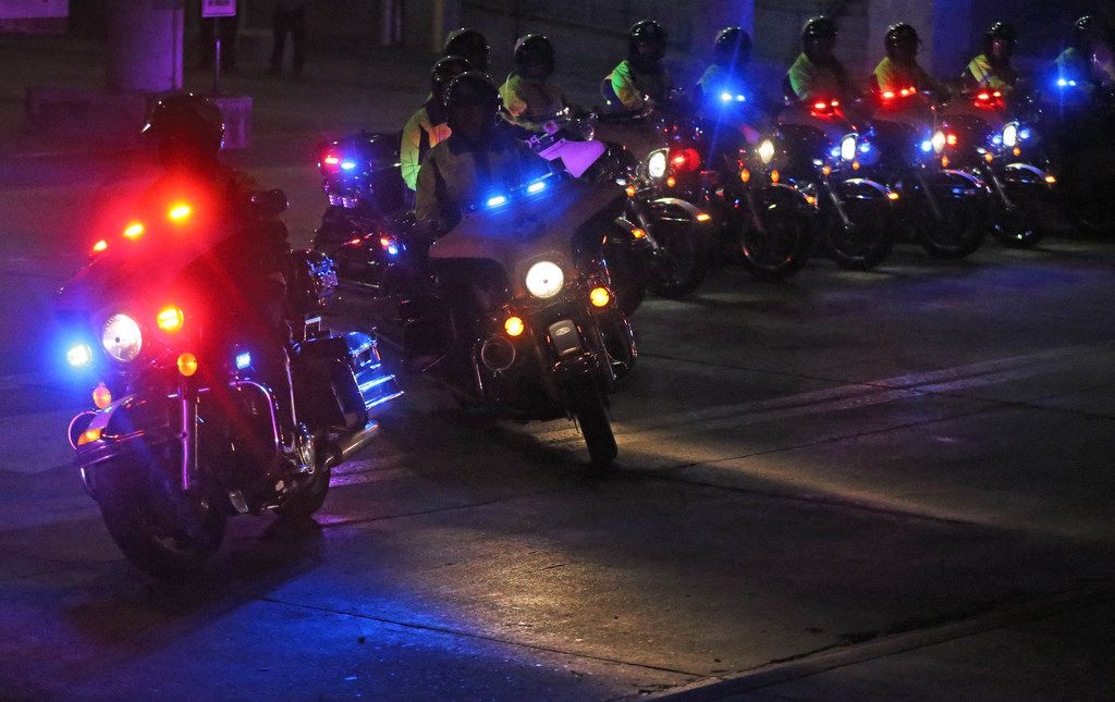Dallas police officers on motorcycles head out to lead the way in the motorcade as the body of slain officer Rogelio Santander Jr. is transported to the medical examiner from Presbyterian Hospital in Dallas in the early morning hours on Friday.