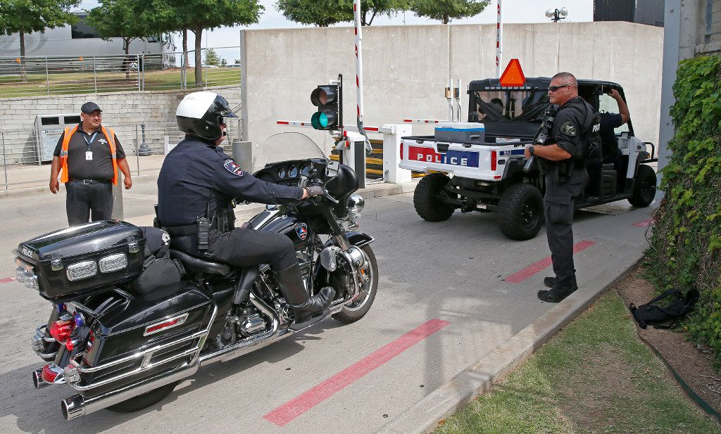 Law enforcement officers enter the AT&T Stadium as an Arlington police officer guards the tunnel entrance before the U2 concert starts in Arlington, Texas, Friday, May 26, 2017. (Jae S. Lee/The Dallas Morning News)
