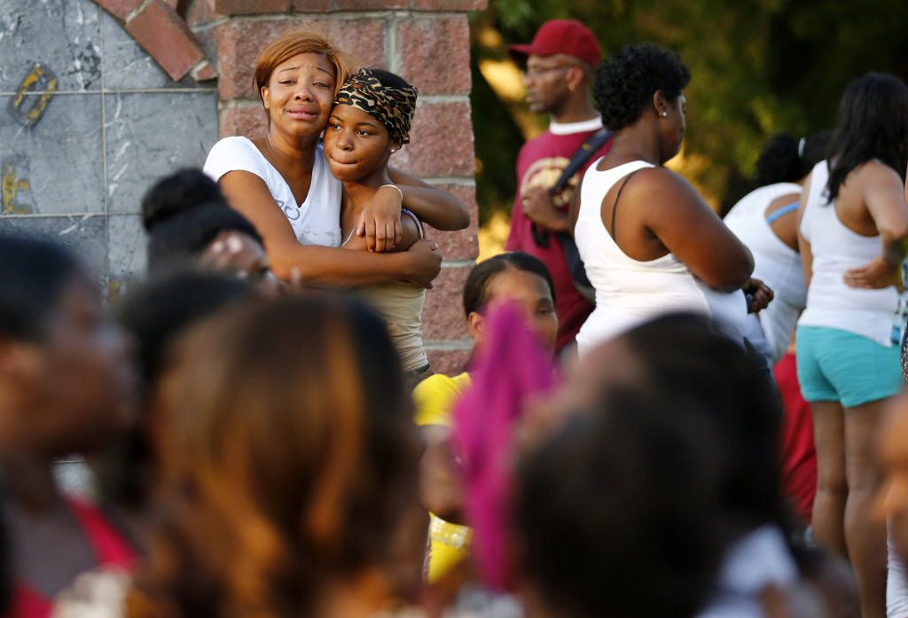 Staneccia Richardson (left), a cousin of shooting victim James Harper, gets comforted by her friend Diamond Robinson after the deadly confrontation in the Dixon Circle neighborhood of South Dallas.