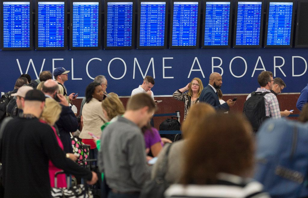 Passengers wait in line to check luggage as flight schedules are projected on screens in Atlanta, Ga, Wednesday, April 5, 2017. Flights have resumed at Atlanta's airport, but stormy weather continues to cause delays for both departing and arriving flights. (David Barnes/Atlanta Journal-Constitution via AP)
