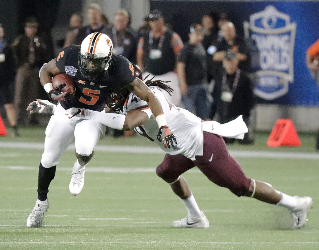 Oklahoma State running back Justice Hill (5) tries to get past Virginia Tech linebacker Tremaine Edmunds during the second half of the Camping World Bowl NCAA college football game Thursday, Dec. 28, 2017, in Orlando, Fla. Oklahoma State won 30-21.(AP Photo/John Raoux)