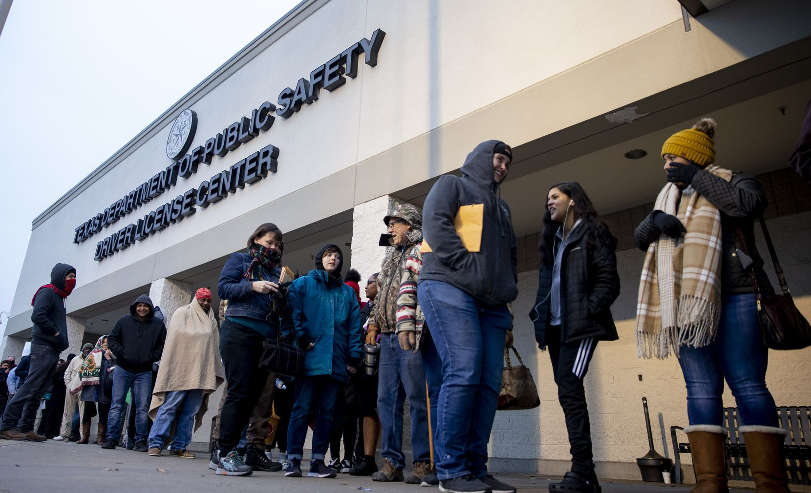 People line up outside the entrance at the Texas Department of Public Safety Driver License in Garland.