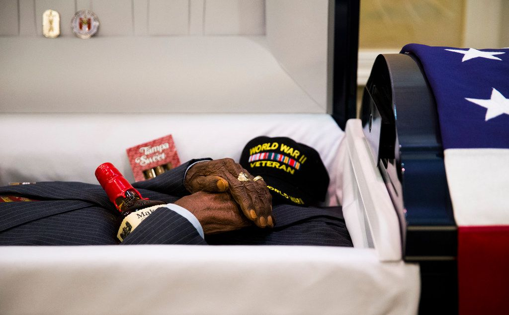 Richard Overton's hands rest on a bottle of Maker's Mark Whiskey and Tampa Sweet cigars lay at his side as his friends and family view his remains at Cook-Walden Funeral Home in Austin on Friday, Jan. 11, 2019, the day before his funeral service and burial. Overton was the oldest living veteran and oldest living male at 112 years old until he died on Dec. 27, 2018. He was known for drinking whiskey and smoking cigars on his front porch in East Austin.