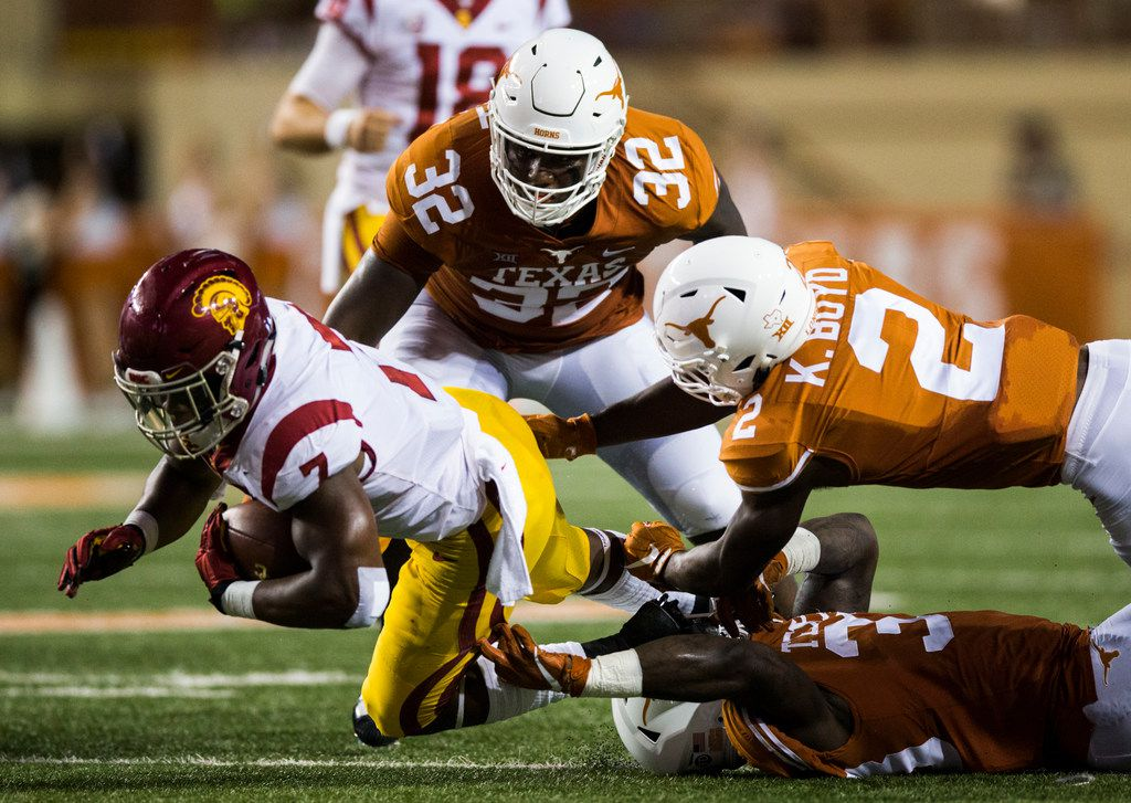USC Trojans running back Stephen Carr (7) is tackled by Texas Longhorns defensive lineman Malcolm Roach (32), linebacker Gary Johnson (33) and defensive back Kris Boyd (2) during the second quarter of an NCAA football game between the Texas Longhorns and the USC Trojans on Saturday, September 15, 2018 at Darrell K Royal Memorial Stadium in Austin, Texas. (Ashley Landis/The Dallas Morning News)