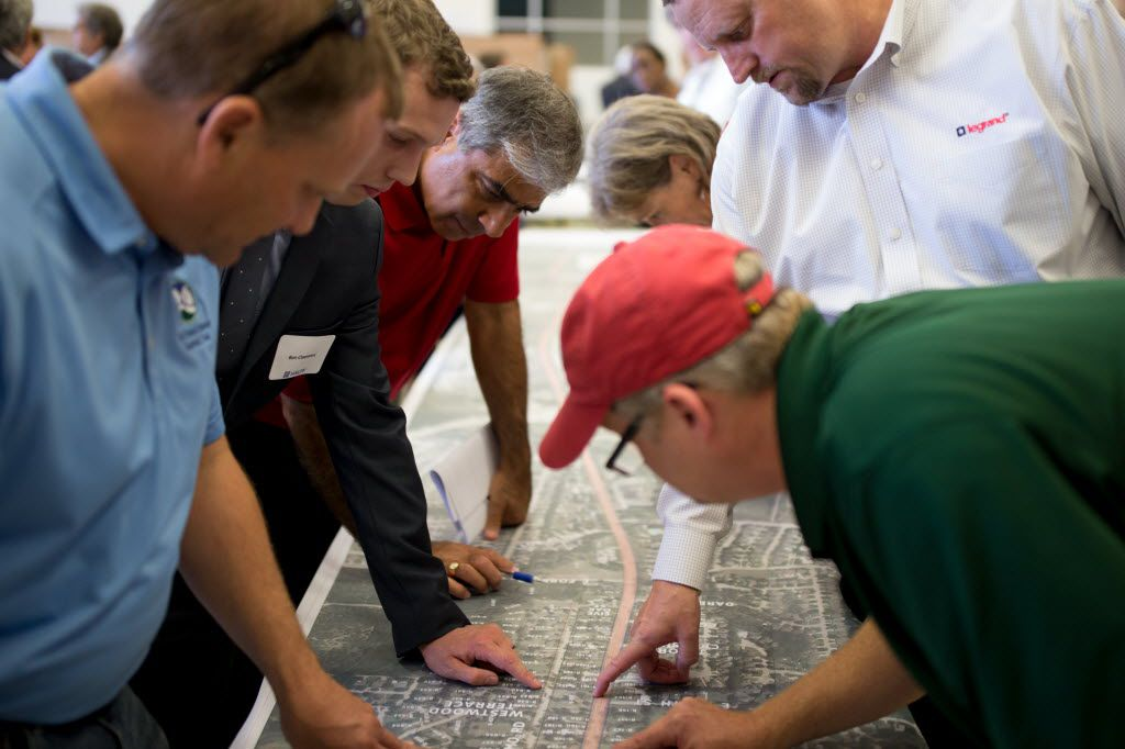 Scott Milder (front left) examines proposals during the public hearing on State Hwy. 205 plans at Utley Middle School on July 7, 2016 in Rockwall.