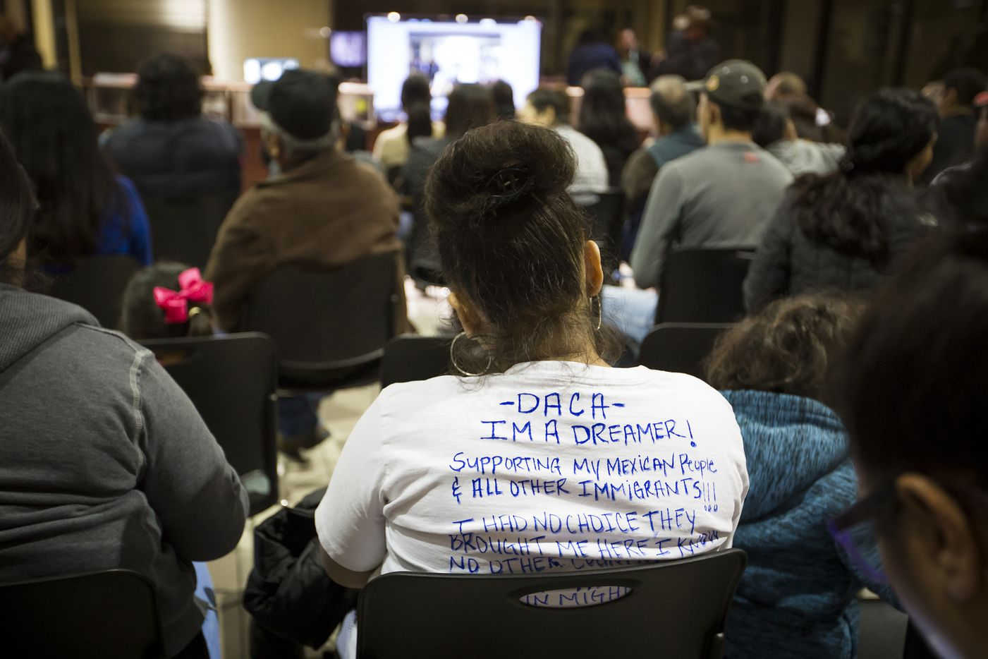 "A woman wears a shirt identifying herself as a ""Dreamer"" (young people effected by the Deferred Action for Childhood Arrivals program) as an overflow crowd spills out into the next room to watch on a television monitor during a community meeting on possible deportations at the Consulate General of Mexico on Thursday, Feb. 16, 2017, in Dallas."