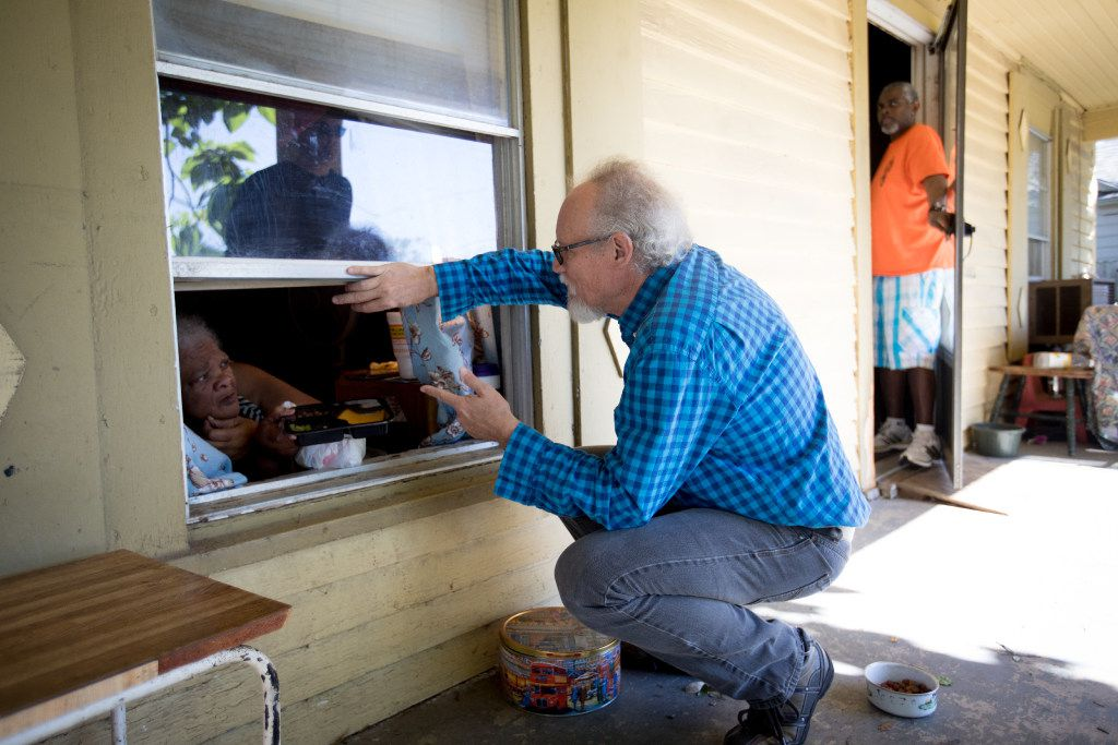 Guy Reynolds talks to Sue Wallace through her bedroom window as he delivers a Meals on Wheels route in South Dallas on Thursday, March 30, 2017. Wallace's son Anthony watches from front door.
