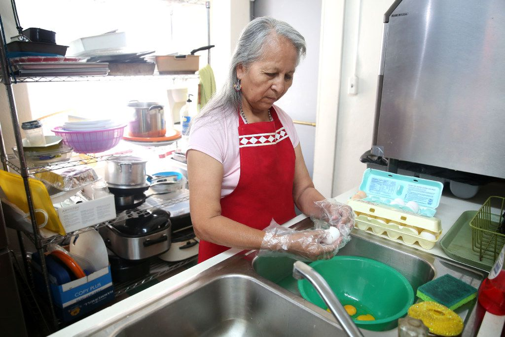 Pauline Lone Fox cracks eggs to combine with a wild onion dish in the kitchen at Dallas Indian Mission United Methodist Church in Dallas on Monday, March 20, 2017. (Rose Baca/The Dallas Morning News)
