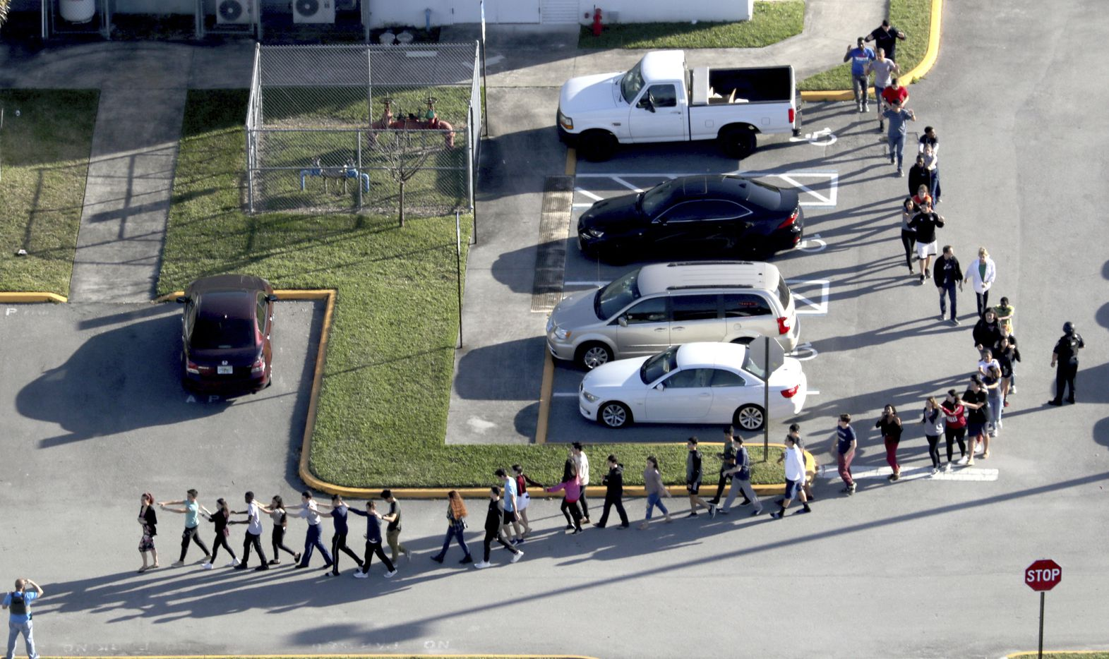 CORRECTS SPELLING TO MARJORY NOT MARJORIE Students are evacuated by police from Marjory Stoneman Douglas High School in Parkland, Fla., on Wednesday, Feb. 14, 2018, after a shooter opened fire on the campus.