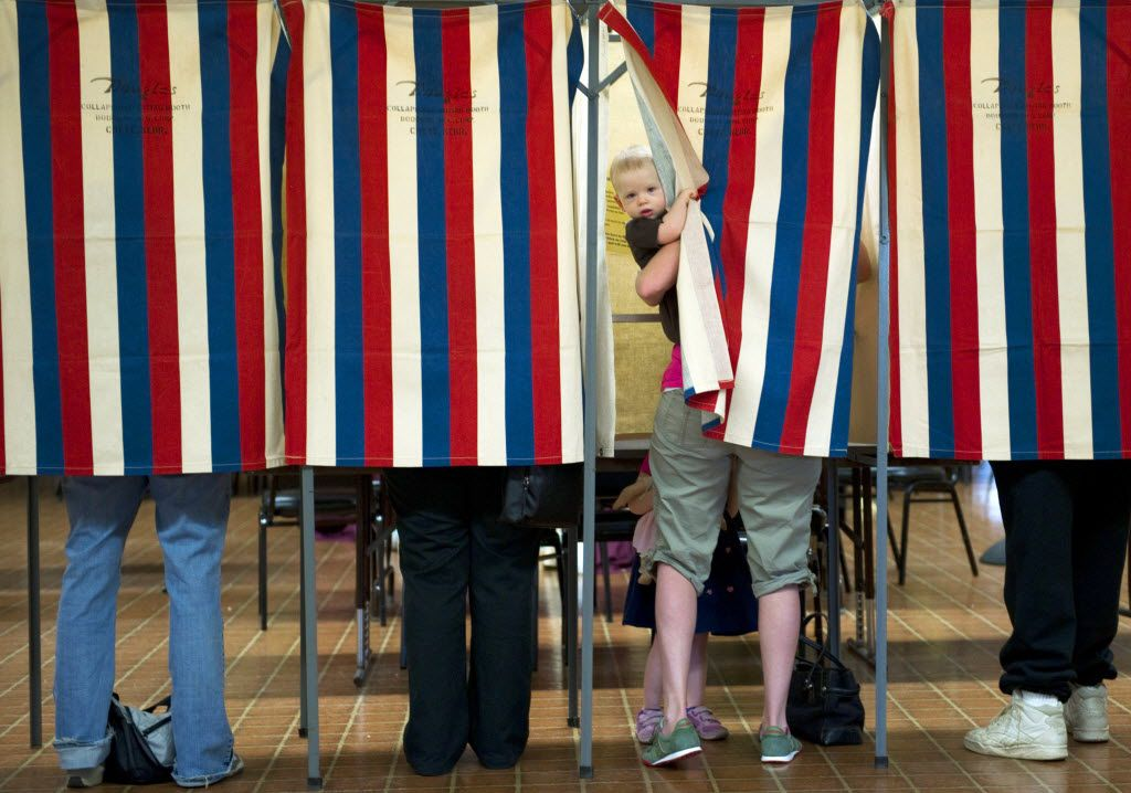 Landon Peterson peeks out of the voting booth while his mother Meghan votes March 20, 2012 at Christian union Church in Metamora, Illinois.